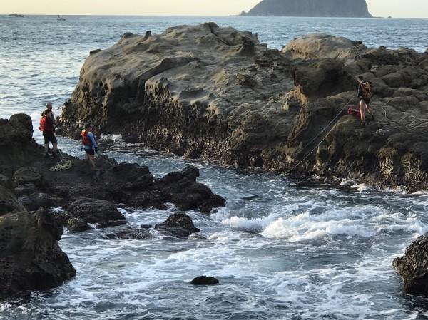 新北市瑞芳區知名景點「酋長岩」周邊岸礁被釣客綁上橫渡繩索、打上鋼釘,消防人員今天到場拆除。(記者林欣漢翻攝)
