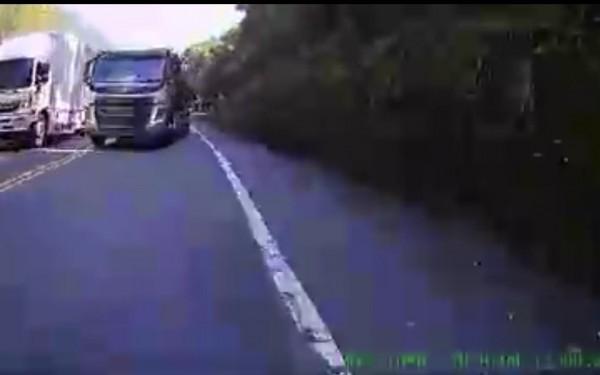 違規雙黃線超車的砂石車毫無退讓之意,逼使重機騎士緊急靠右,險些掉進旁邊水溝。(記者佟振國翻攝)