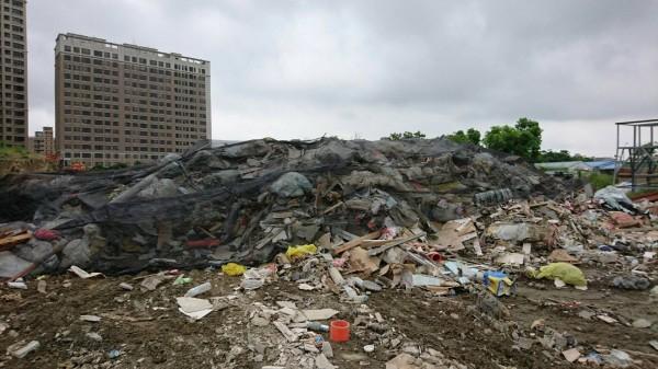 新竹縣健康產業園區預定年底啟用營運,但周邊住戶抱怨,中醫大在工地內堆置「垃圾」,數量越積越多,居民感覺蚊蠅變多了,擔心危害環境衛生。(記者廖雪茹翻攝)