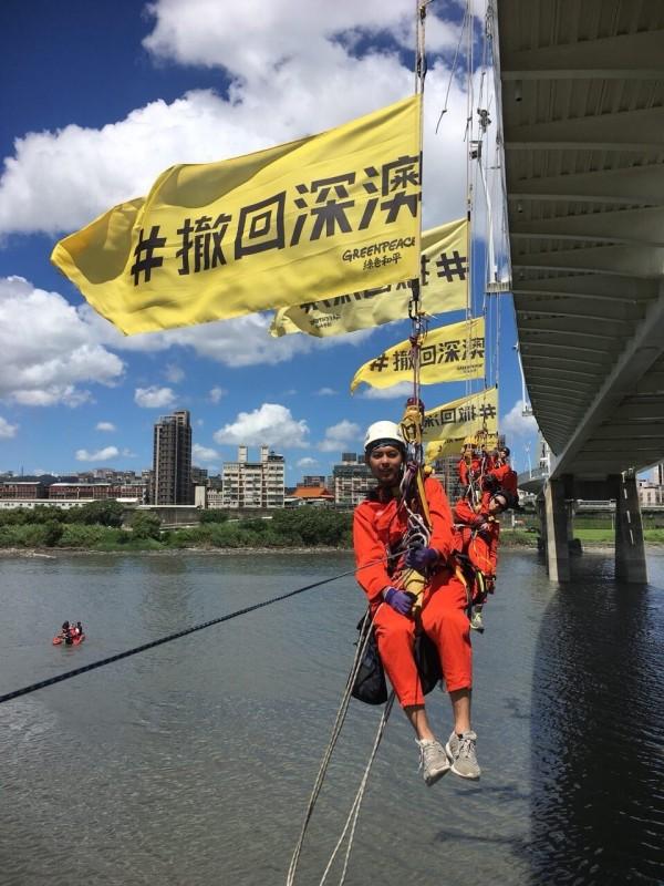 綠色和平人員吊掛在新月橋上,表達「撤回深澳」的訴求;水面可見遊艇戒護中。(圖由綠色和平組織提供)