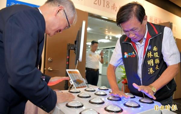 南投縣長林明溱(右)與竹山秀傳醫院院長謝輝龍(左),一起體驗「按燈認知」遊戲情形。(記者謝介裕攝)