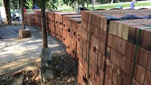 滿載磚塊的拖板車突然車頭、車身分離,緊急把車斗上的磚塊吊至路旁。(記者湯世名翻攝)
