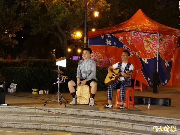楊文科團隊「藝起來飛楊」首場藝文活動,今晚邀請到藝人民雄和在地的Mr.One Cajon樂團,共同以民謠吉他和木箱鼓,交織美妙的旋律及歌聲,吸引民眾佇足欣賞。(記者廖雪茹攝)