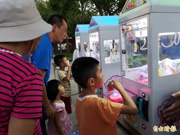 「青春飛楊號」改造胖卡車載來夾娃娃機、扭蛋機,主辦單位提供打卡按讚兌換代幣,吸引不少親子試身手。(記者廖雪茹攝)