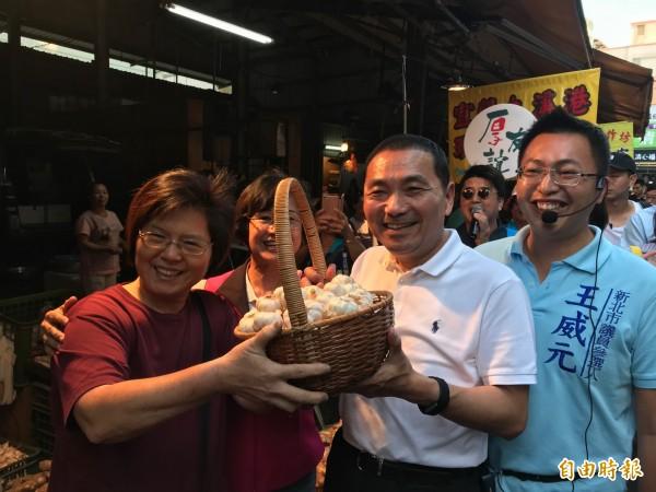 黃昏市場攤商熱情送上一籃象徵凍蒜的大蒜。(記者陳心瑜攝)