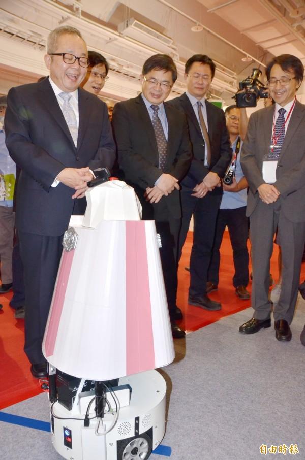 行政院副院長施俊吉(左一)參觀嘉南藥理大學研發團隊的「居家安控機器人」,對於展示的功能,相當滿意,笑得合不攏嘴。(記者吳俊鋒攝)