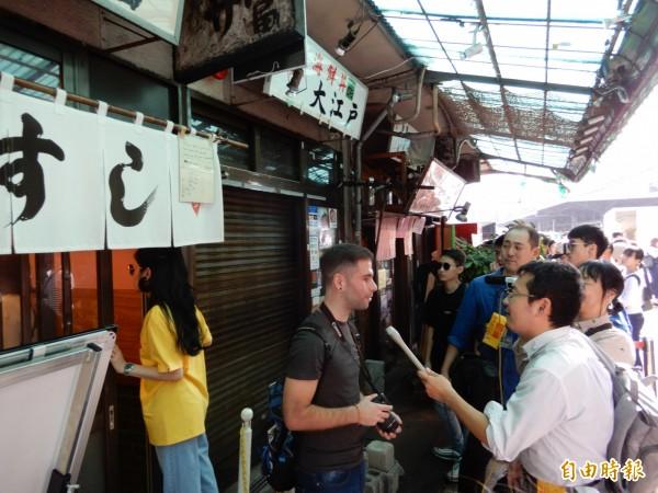 日本媒體在場外餐飲店前訪問西班牙旅客。(記者林翠儀攝)