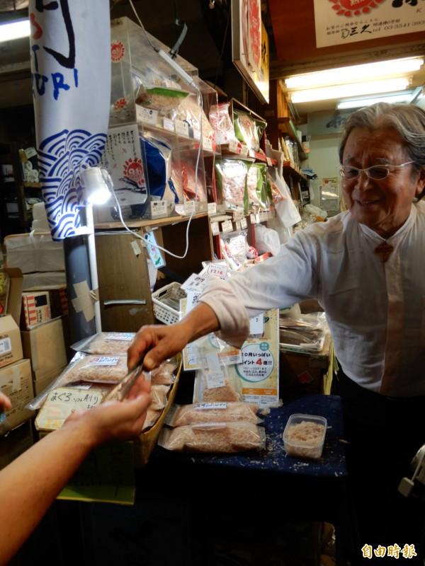 柴魚乾貨店「和田久」的老闆在門口請大家試吃柴魚。(記者林翠儀攝)