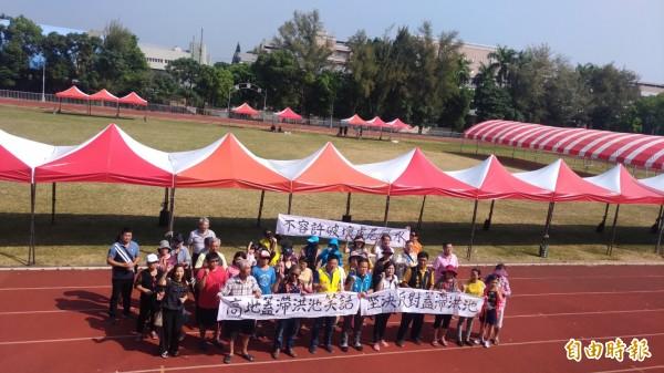 現場民眾簽署抗議書,並手舉「拒絕虎尾體育場設置滯洪池」的白布條。(記者廖淑玲攝)