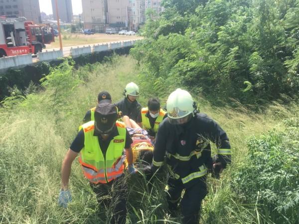 金門縣消防局金城分隊將女大生從大排水溝底的草叢中,以擔架救出來。(金門縣消防局金城分隊提供)