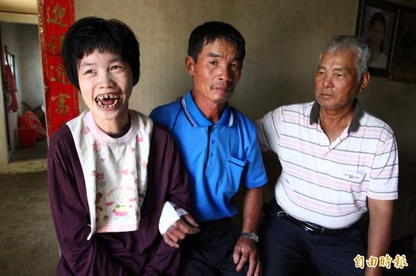 陳江游(中)是單親爸爸照顧腦性麻痺的女兒(左),官順村長陳樹成(右)希望各界幫忙他們母女。(記者林宜樟攝)
