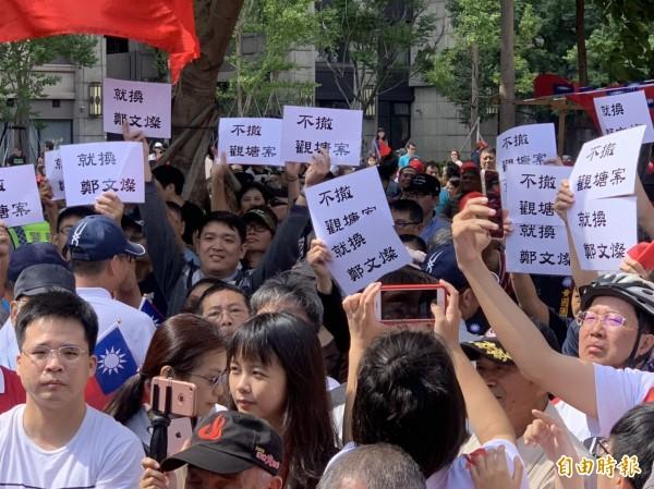 抗議人士高舉抗議標語。(記者許倬勛攝)