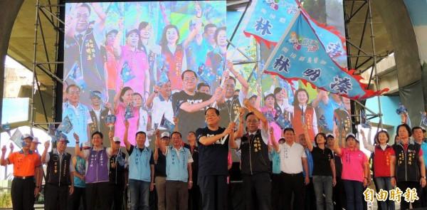 國民黨副主席曾永權(左)在競選總部成立大會中為南投縣長候選人林明溱(右)授旗情形。(記者謝介裕攝)