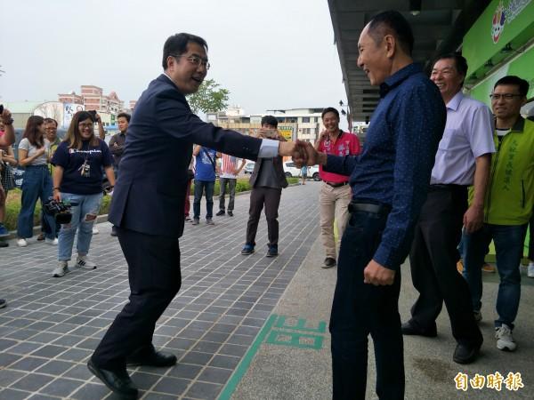 林義豐在進入城市願景館時,2人互跨「38度線」。(記者邱灝唐攝)