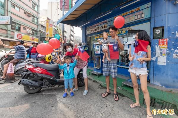 沿途民眾也高舉小國旗和氣球同樂。(記者廖淑玲攝)