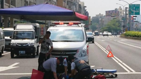熱心的「大傘哥」搬來巨大洋傘替車禍受傷的婦人和救護人員遮陽。(記者黃佳琳翻攝)