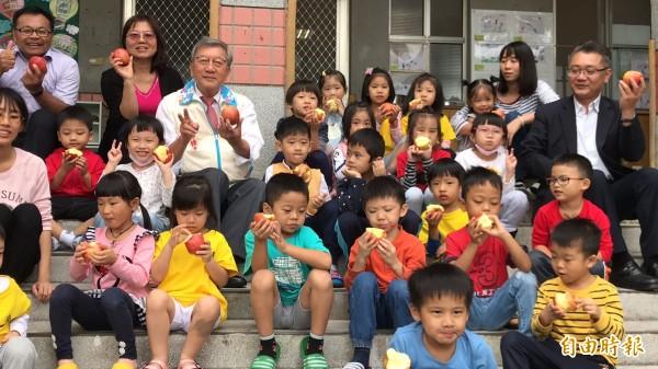 新竹縣東海國小附設幼兒園的小朋友們個個忙著啃蘋果,忘了跟縣長阿公合照要看鏡頭。(記者黃美珠攝)
