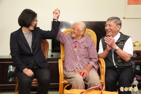 邱張桂英(中)舉起蔡英文的手,稱讚她是好總統。(記者張軒哲攝)