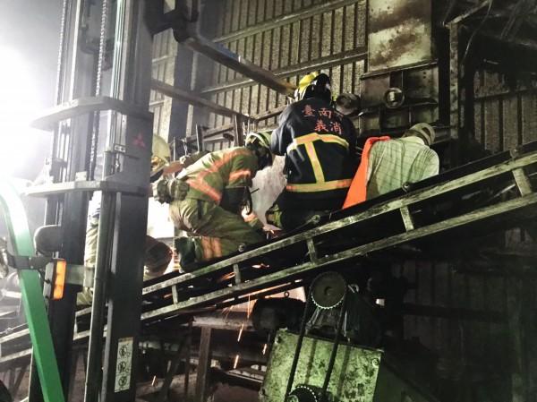 民眾左腳捲入輸送帶,消防隊員緊急救原。(記者吳俊鋒翻攝)