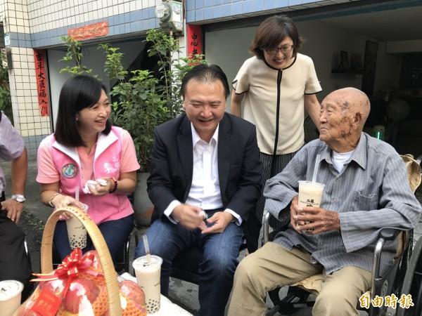 112歲王寶華(右)是全國最高齡男性,許立明(前中)賀節並請教養生之道。(記者洪臣宏攝)