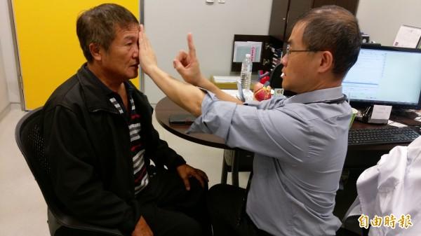 長安醫院心臟血管科李愛先醫師(右)替張先生(左)進行「頭頸部血管支架置放術」後,回診檢查發現頭暈、複視等症狀都消失。(記者陳建志攝)