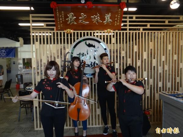 台南市南區永成路八六山雞城店員伙伴能瞬間化身中、西合璧小樂團樂手為顧客獻奏美妙樂曲。(記者王俊忠攝)