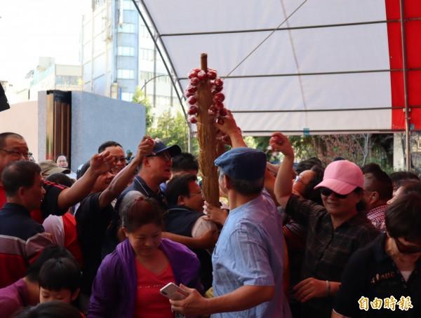 葫蘆墩圳景觀環境營造工程啟用典禮,主辦單位特別準備了冰糖葫蘆發送,民眾爭相索取。(記者歐素美攝)