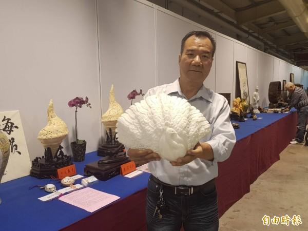 蔡振昌在純白的硨磲上精雕成「孔雀開屏」。(記者鄭旭凱攝)