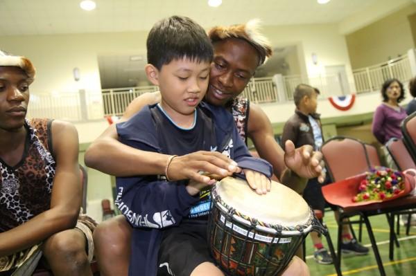 辛巴威Umkhathi劇團成員教豐洲國小學童打非洲鼓。(市府提供)