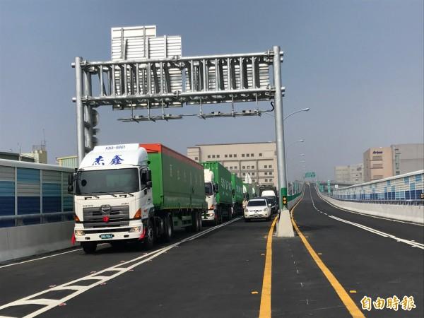 高雄港聯外高架道路今天全線通車,聯結車通過時齊鳴喇叭祝賀。(記者洪臣宏攝)