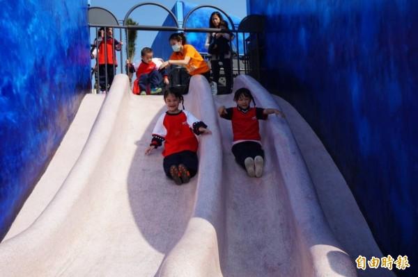 八里商港公園的鯨魚造型地景溜滑梯今天啟用,小朋友玩得不亦樂乎。(記者葉冠妤攝)
