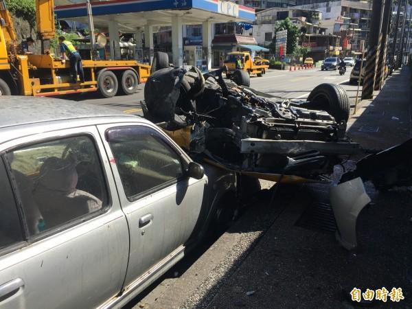 計程車翻覆時撞上路旁臨停車輛(記者吳昇儒攝)
