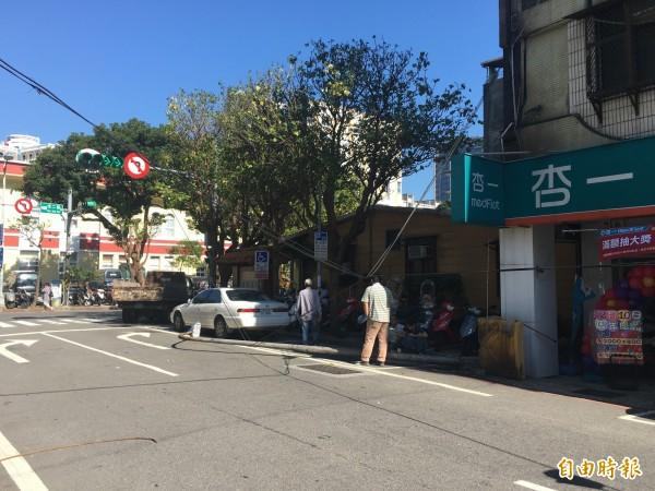 基隆市義四路上藥妝店前的路燈,今天接近中午12點時,突然無預警倒下,所幸天空中的纜線、電線將路燈桿攔下,讓路燈桿未倒在馬路上。(記者俞肇福攝)