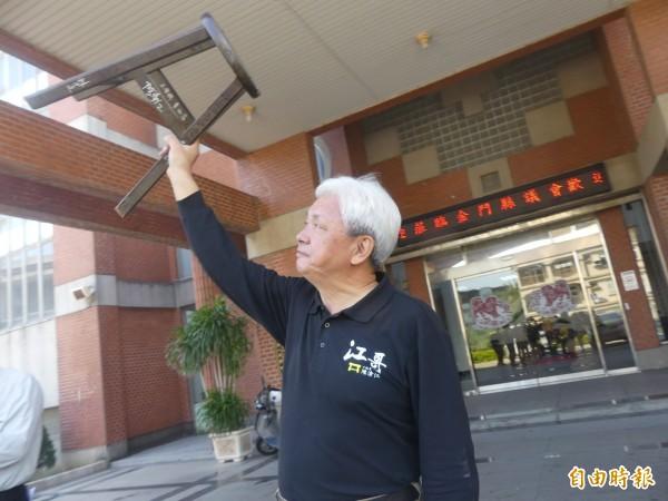 金門縣議員陳滄江「深情」望著陪他度過8年議員生涯的小板凳。(記者吳正庭攝)