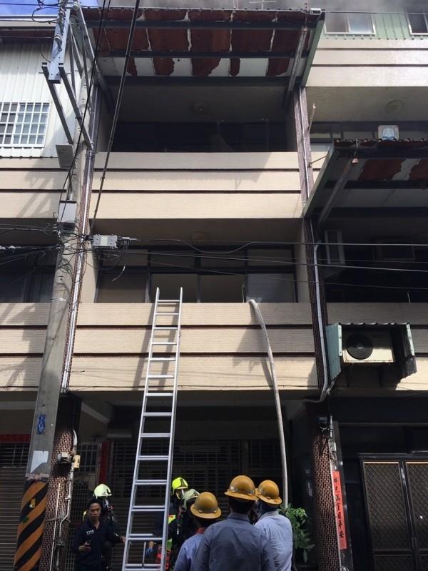 大甲區中華街一處民宅發生火警,消防人員攀梯從二樓進入灌救。(記者歐素美翻攝)