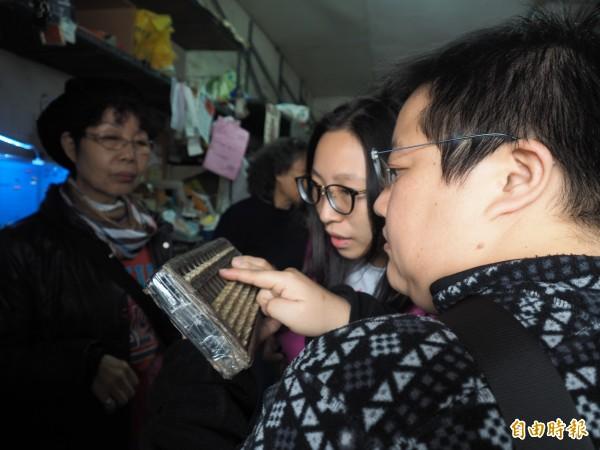 遊客好奇地研究起雜貨店使用40年的算盤。(記者王秀亭攝)