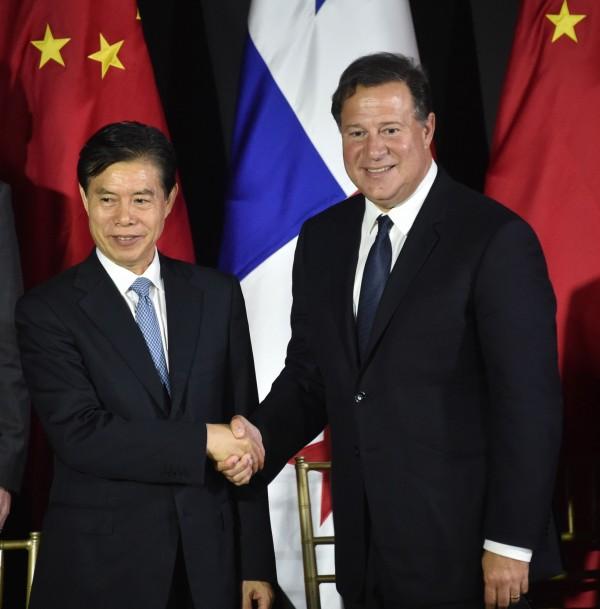 中國商務部長鍾山(左)昨於巴拿馬市與巴拿馬商務部長簽訂合作協議,右為巴拿馬總統瓦雷拉。(法新社)