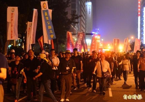 監督年金改革行動聯盟18日號召來自全台各地的抗議民眾至立法院夜宿。圖為抗議群眾晚間集體繞行立法院。(記者王藝菘攝)