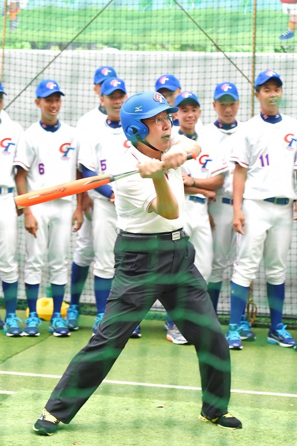Taipei Mayor Ko Wen-je, front, on Saturday takes aim at a ball during a flag presentation ceremony at Taipei's Dongyuan Elementary School ahead of this year's Little League Baseball Asia-Pacific Regional Tournament in South Korea. Photo: Liu Hsin-de, Taipei Times