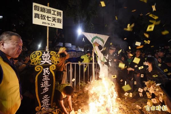 勞團聚集於立法院青島東路側門,燃燒冥紙抗議民進黨強推砍7天假法案。(記者陳志曲攝)
