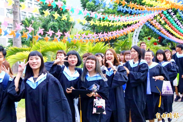 Chaoyang University of Technology students stand under a dream catcher made of 5,000 pinwheels that decorated the campus yesterday.