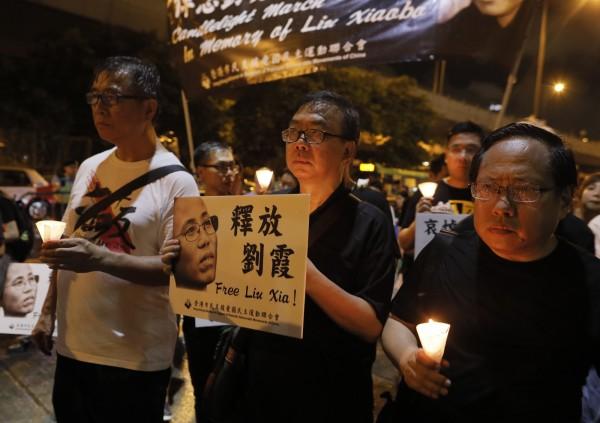 為哀悼中國民主鬥士劉曉波過世,香港支聯會於週六晚間舉行燭光遊行,,參與民眾不畏雨勢,以鮮花與燭光向劉曉波致意。(美聯社)