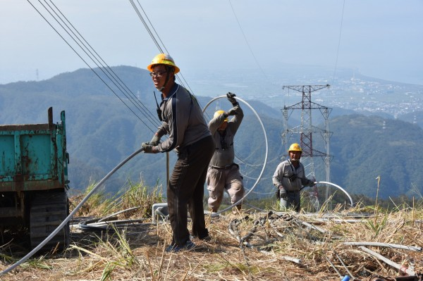 搶修和平電廠電塔,電塔間的導體重量相當重,維修人員必須先延放直徑約與原子筆芯一樣細的較輕引線開始,再牽引細尼龍線、粗尼龍線、鋼絲,逐步作業,最後才以鋼絲牽引真正的纜線。(經濟部提供)