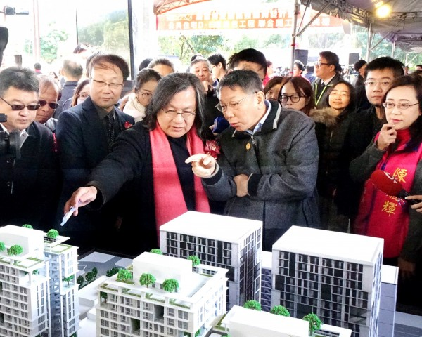 Taipei Mayor Ko Wen-je, center right, yesterday points to housing models at a ground-breaking ceremony for a public housing construction project in Xinyi District. Photo: Fang Pin-chao, Taipei Times