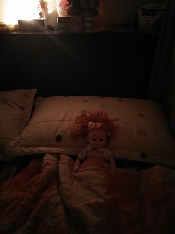 雙人床女兒睡覺的位置只剩下取名為「莎拉」的娃娃,爭著眼睛、蓋著棉被躺在那。(圖擷取自爆廢公社)