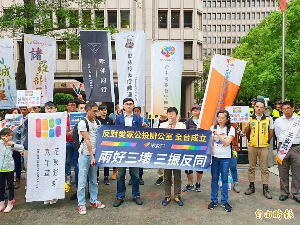 Members of pro-marriage equality groups hold up banners with slogans at a news conference in front of the Central Election Commission in Taipei yesterday. Photo: Li Hsin-fang, Taipei Times