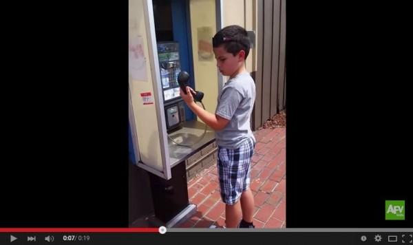 一名男童初見投幣式公共電話,露出困惑不解的神情,網友看了都不禁嘆:「唉!我們都老了!」(圖取自YouTube)