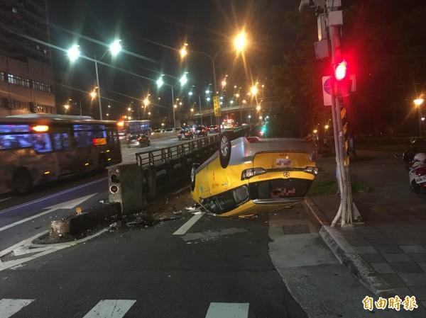 63歲王姓運將載今晚載3名香港遊客,因自身低血糖突然昏迷,撞上忠孝橋橋墩翻車,車內4人一度受困。(記者陳恩惠攝)