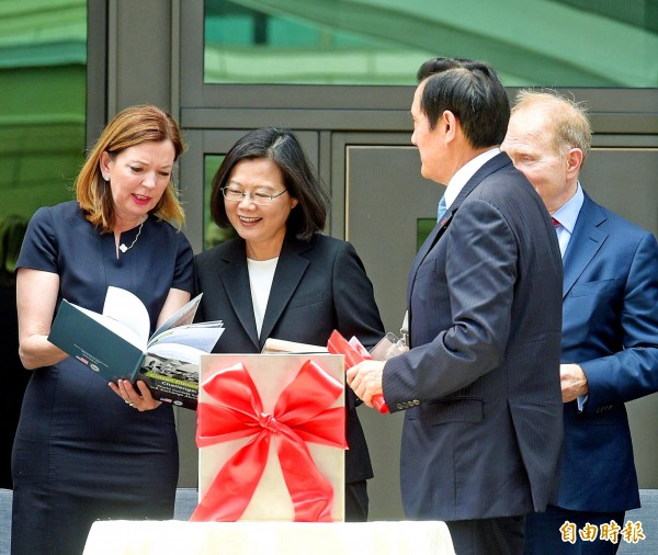 US Assistant Secretary of State for Educational and Cultural Affairs Marie Royce, left, shows President Tsai Ing-wen, center, a book about her bureau's international exchange program as US Department of State Bureau of Overseas Buildings Operations Principal Deputy Director Ambassador William Moser, right, and former president Ma Ying-jeou look on during the dedication of the new American Institute in Taiwan complex in Taipei yesterday. Photo: Chang Chia-ming, Taipei Times