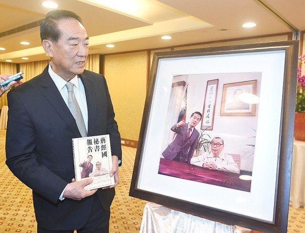 People First Party Chairman James Soong holds a copy of his new book while standing in front of a picture of himself with former president Chiang Ching-kuo at a news conference at the Evergreen Laurel Hotel in Taipei yesterday. Photo: Liao Chen-huei, Taipei Times